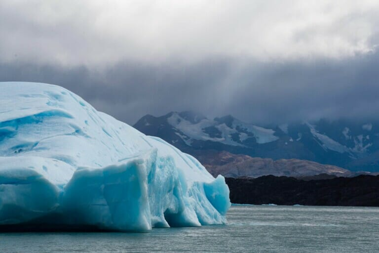 A huge bright blue iceberg floats in the water of a lake in Argentina