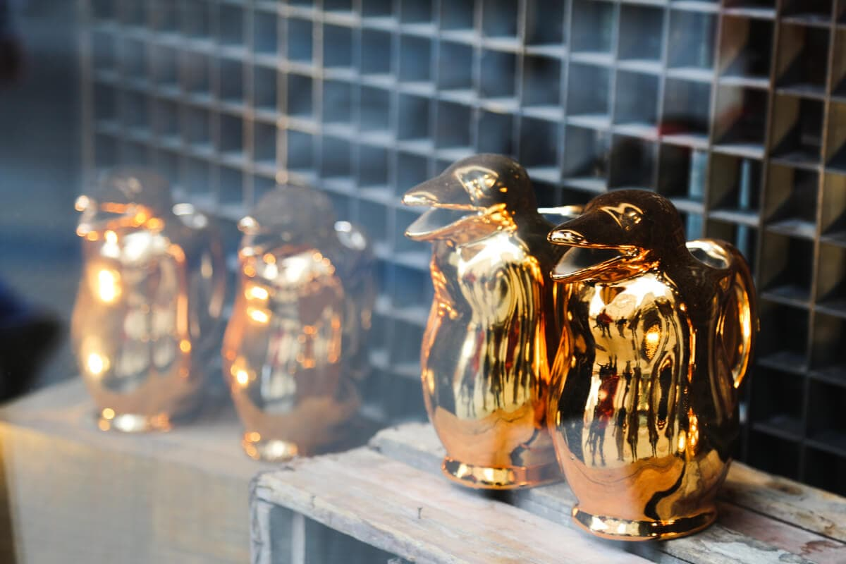 Four golden pitchers in the shape of penguins in a storefront window
