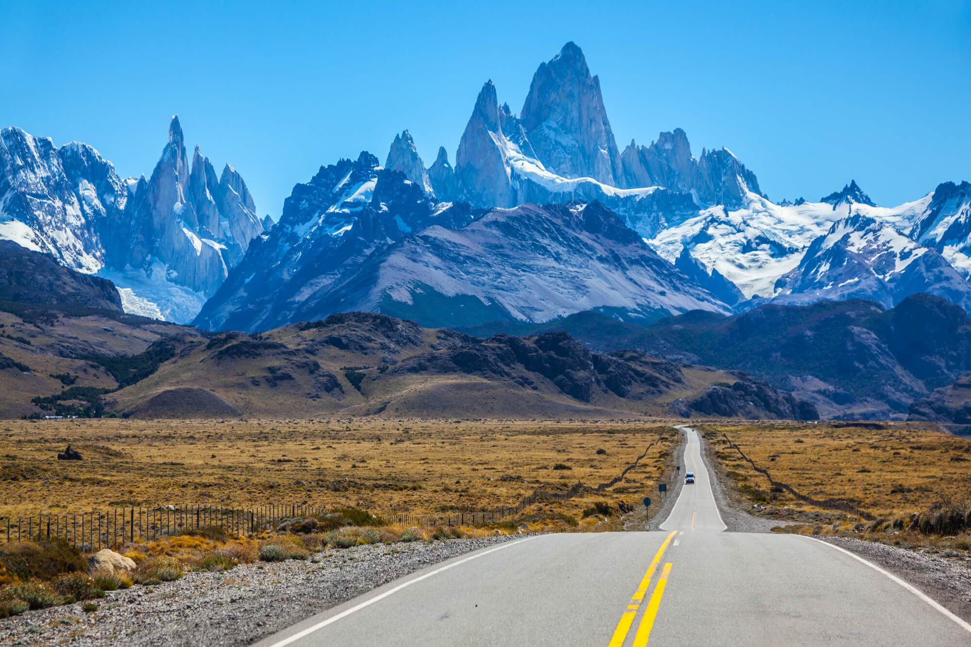 A highway leads from the photographer to a mountain range of rocky peaks and a bright blue sky.