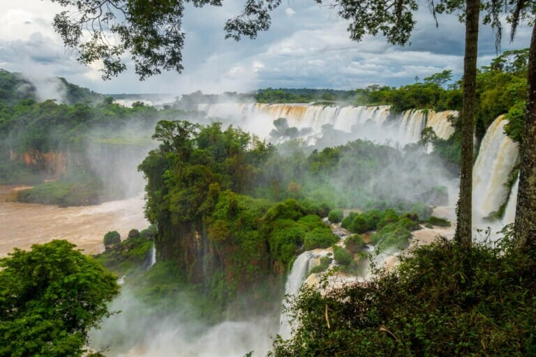 A line of waterfalls of brown water pour down in a green jungle with mist rising up from the river below