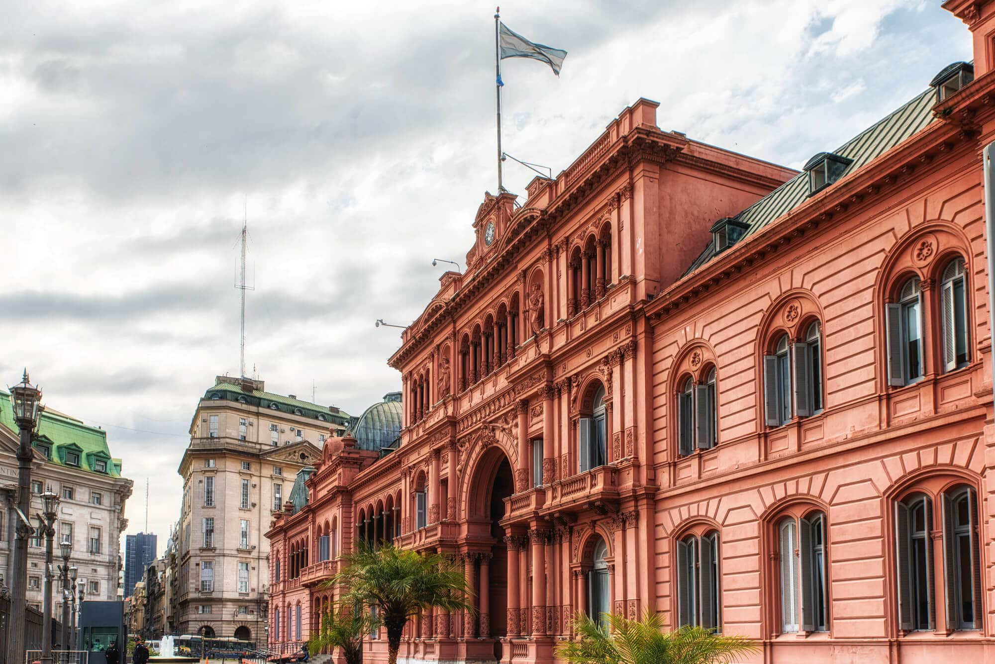 A pink government building with a blue and white flag flying overhead