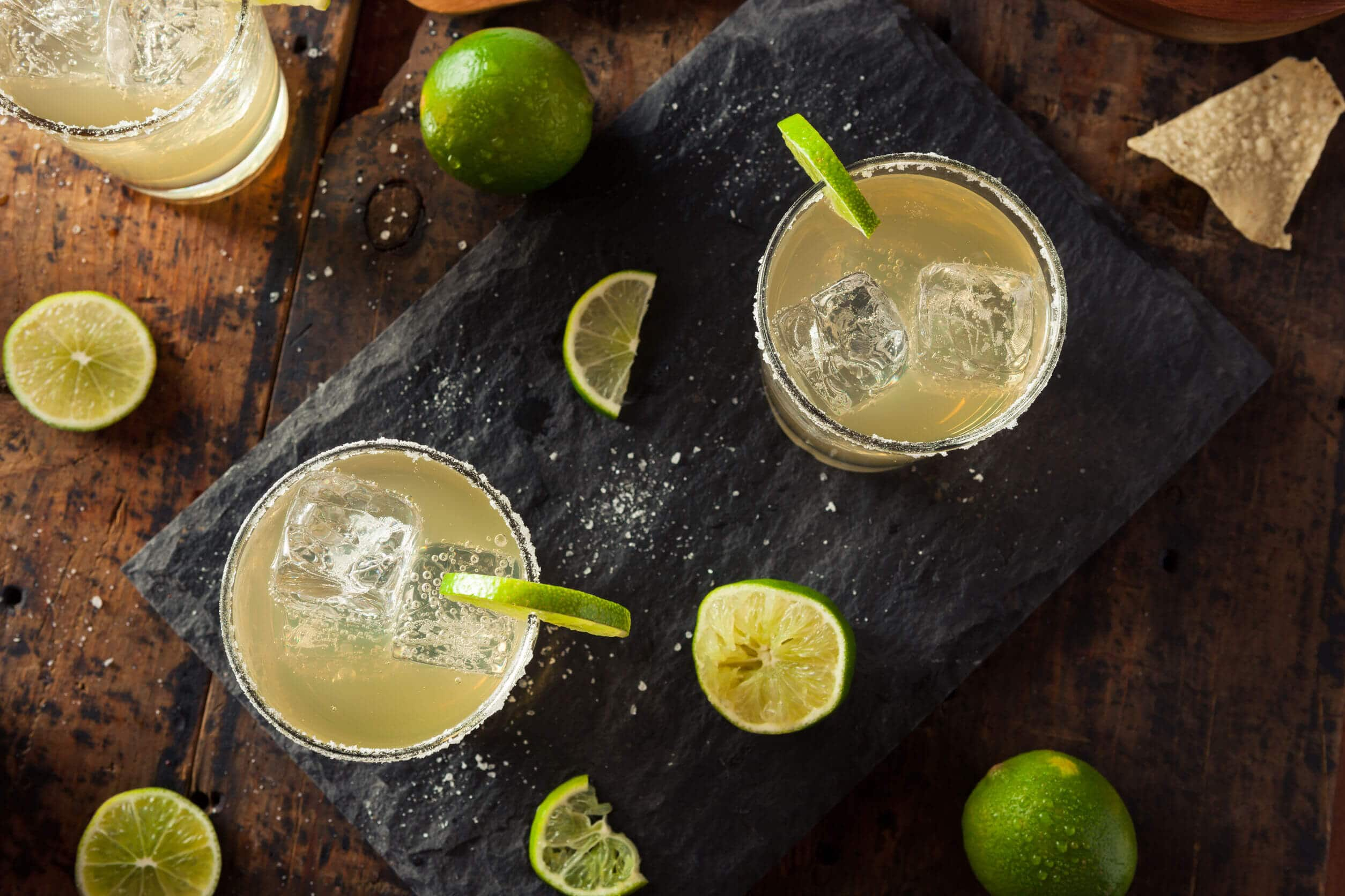 Two margaritas on the rocks on a stone serving platter surrounded by limes