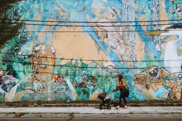 A woman pushes a stroller in front of a mural