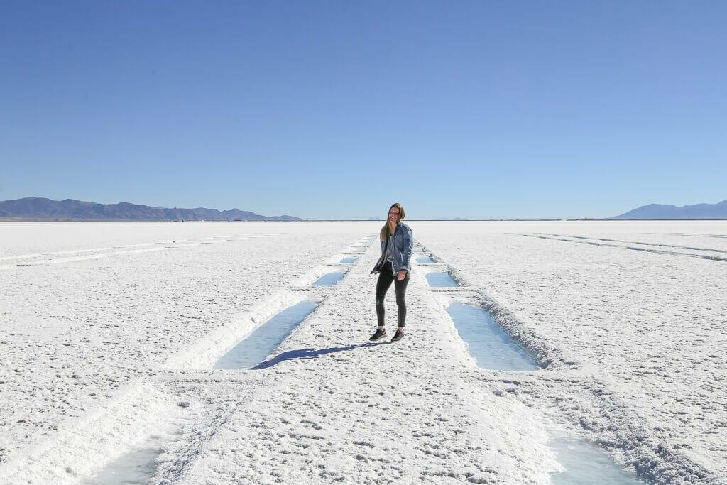 A woman walking on bright white salt in Argentina' salt flats
