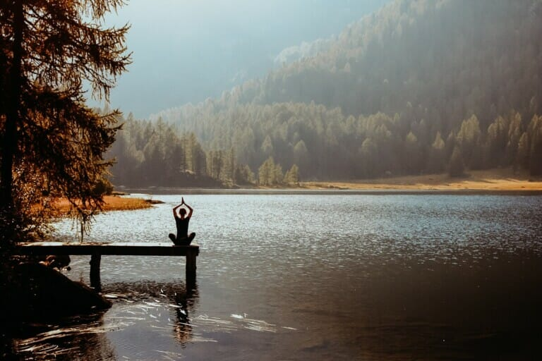 A woman sits on a wooden pier doing yoga by a forest