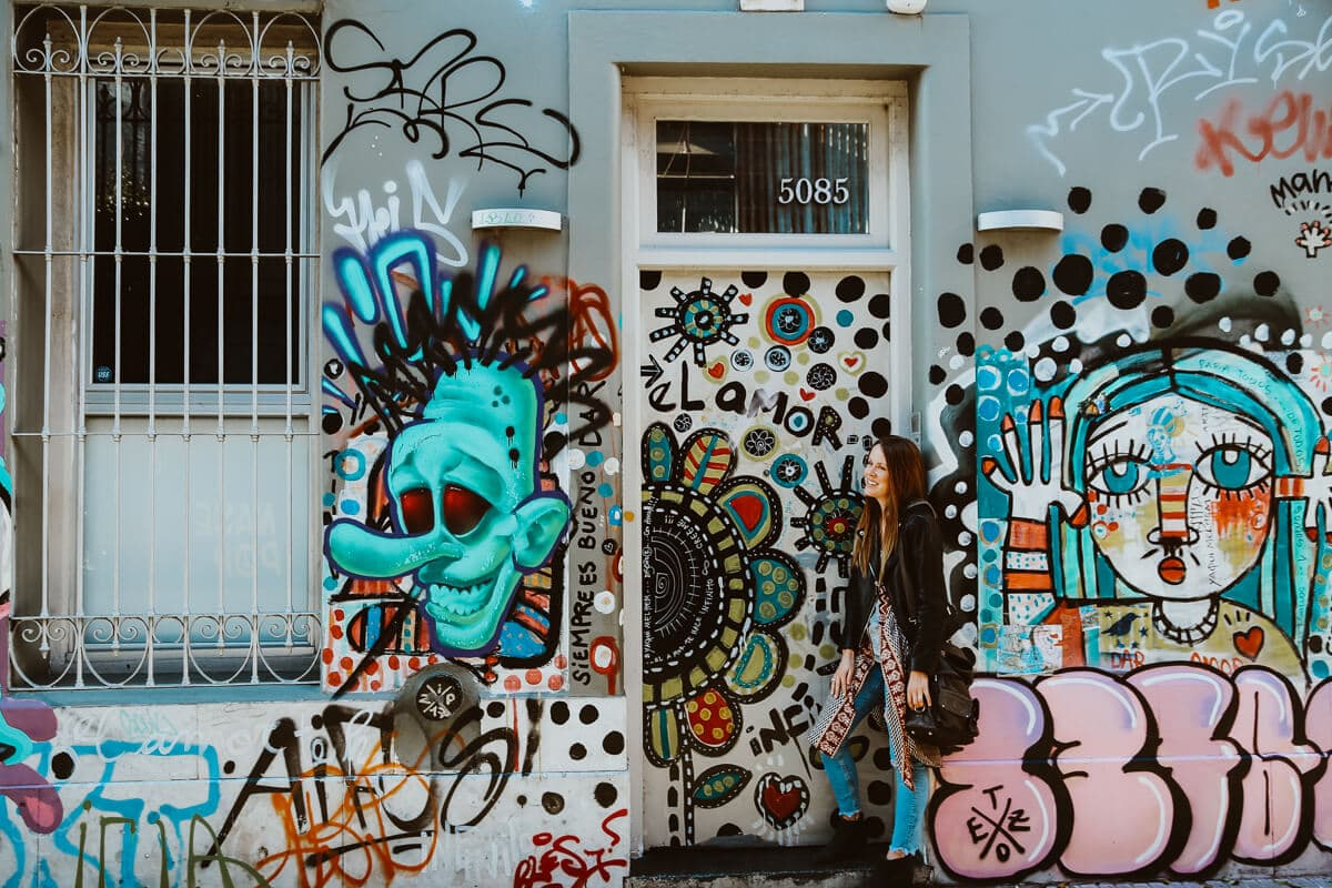 A woman in a black leather coat stands in front of a graffiti covered wall leaning on a door frame