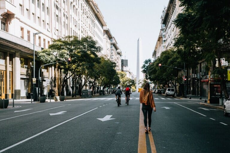 A woman walks away from the camera down the middle of a street towards an obelisk
