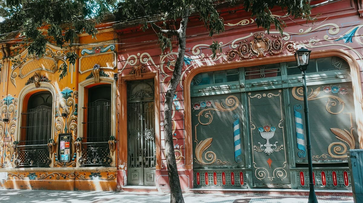 Two colonial style buildings covered in the floral swirly Fileteado style of painting typical to Buenos Aires