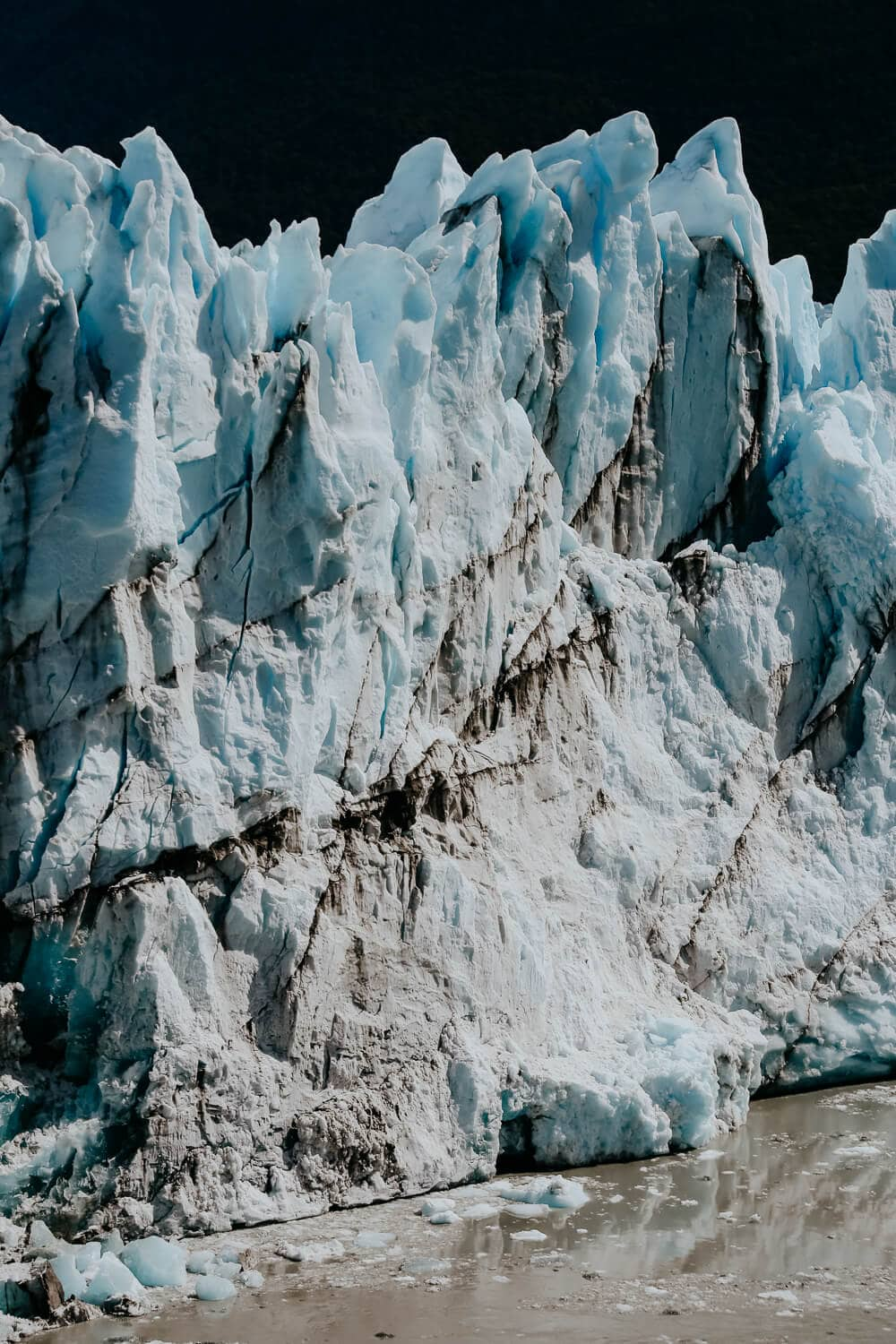 A wall of turquoise blue ice covered with dirt.