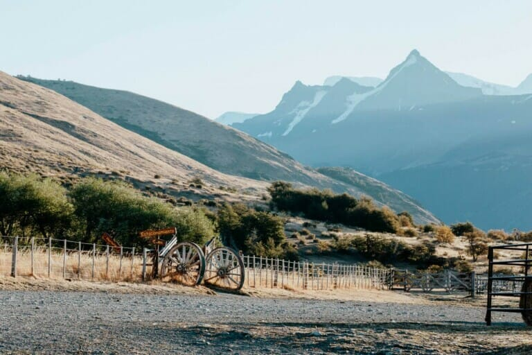 A dirt road passes by a wire fence with a mountain range in the background