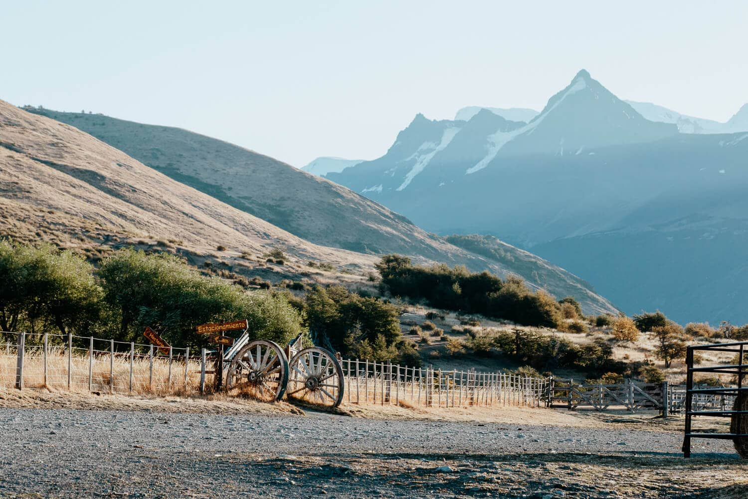 Mountains in the background are bathed in the sunset behind a fence at an El Calafate ranch.