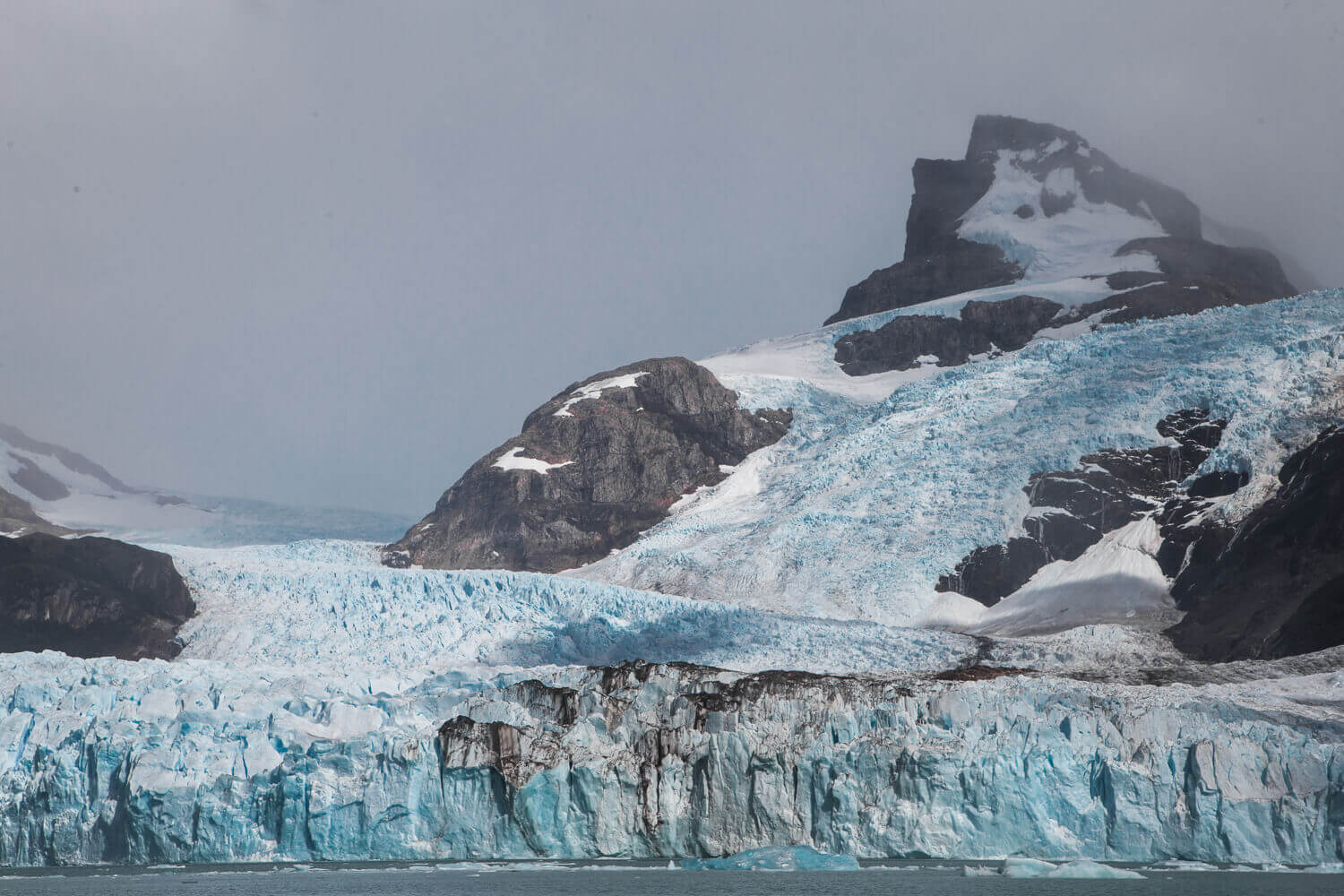 A grey mountain is blanketed in a turquoise blue glacier that climbs down from the peak to meet the water below.