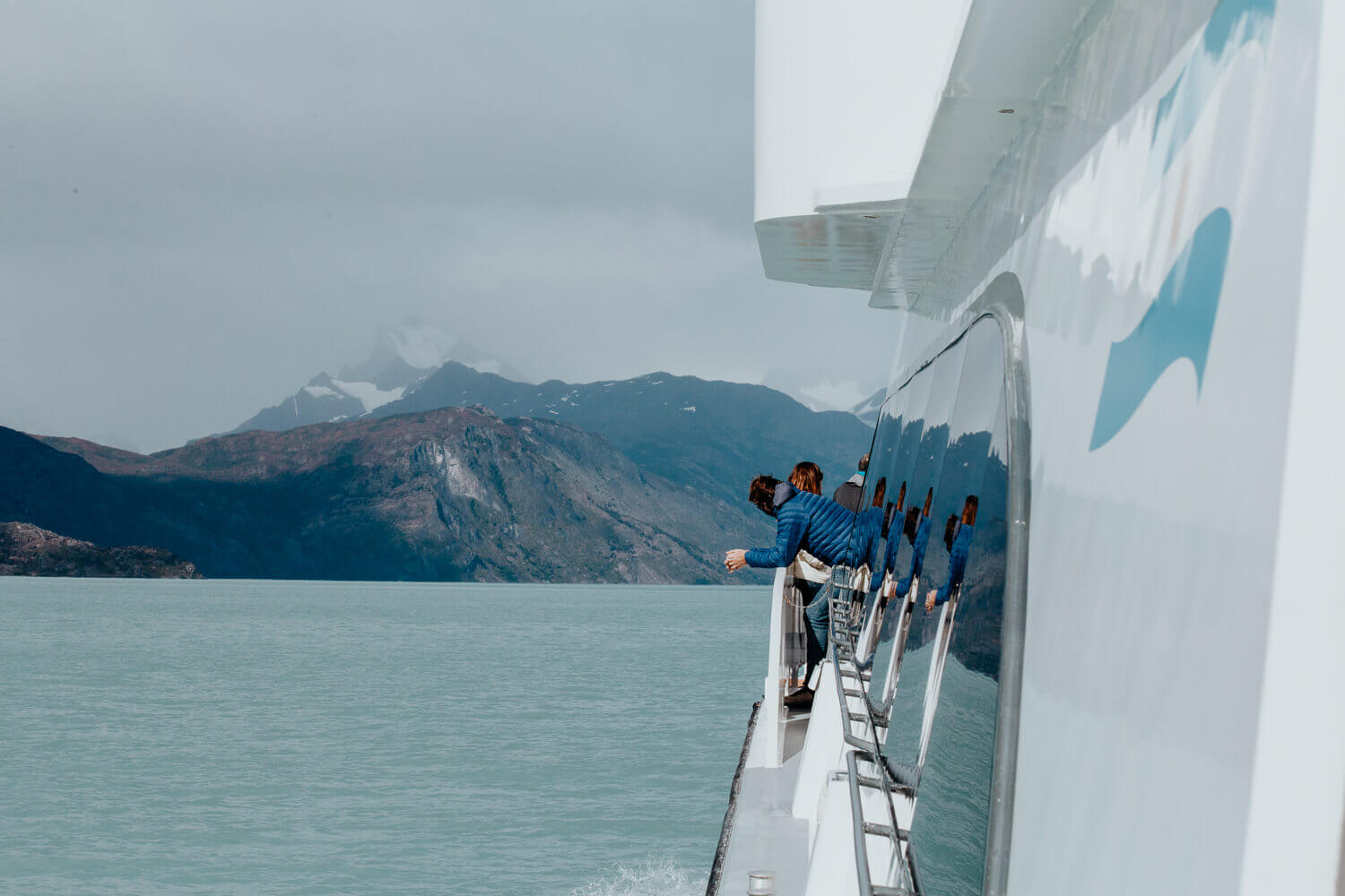 A man in a blue coat leans against the rail of a catamaran watching the mountains in the distance.