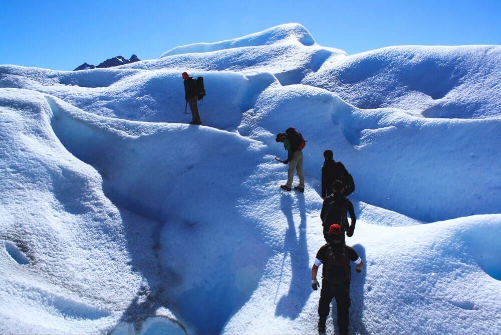 5 men with ice picks climb a snow bank on a glacier in El Calafate Argentina