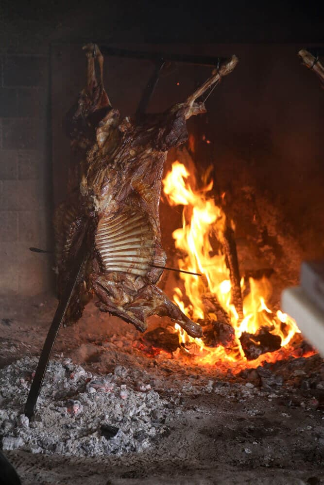A rack of lamb roasts over an open fire on a metal cross.