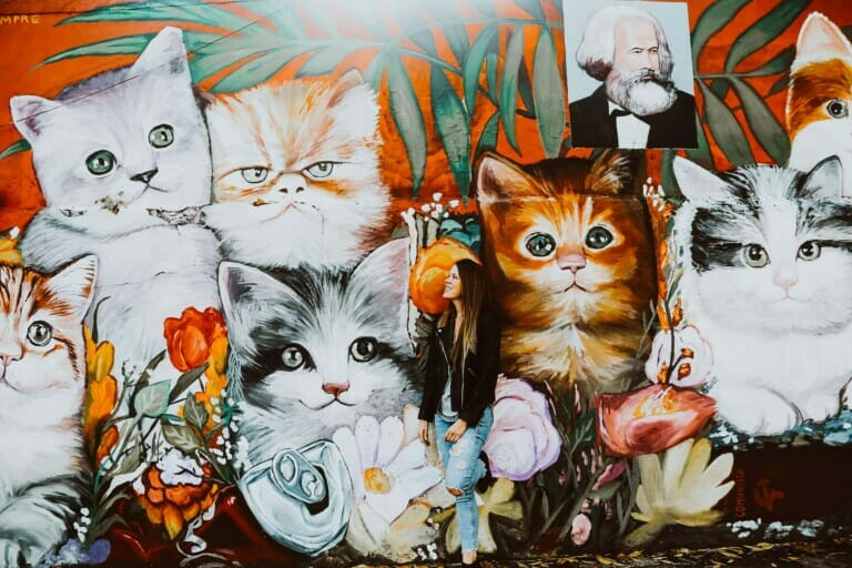 A woman leans against a wall covered in a mural of kittens