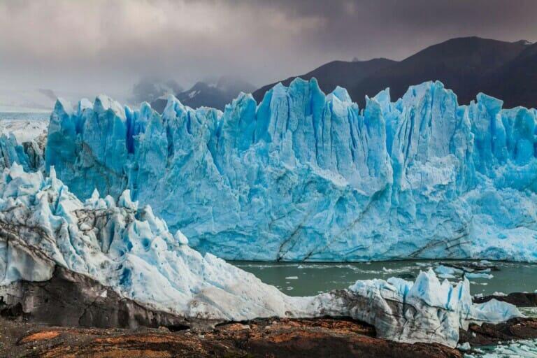 A bright blue glacier on a cloudy day