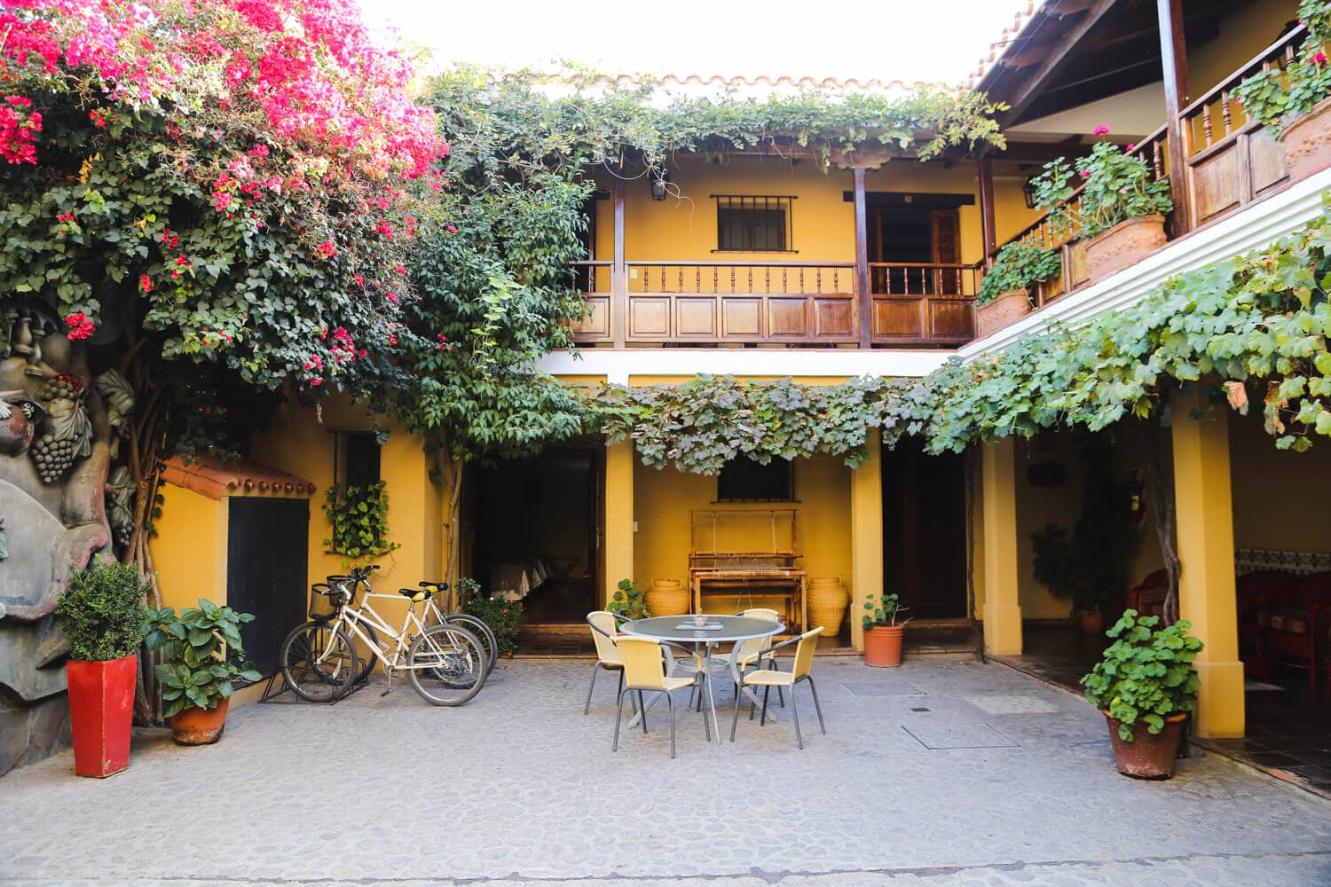 Bicycles and a table sit in the courtyard of a two story colonial style home