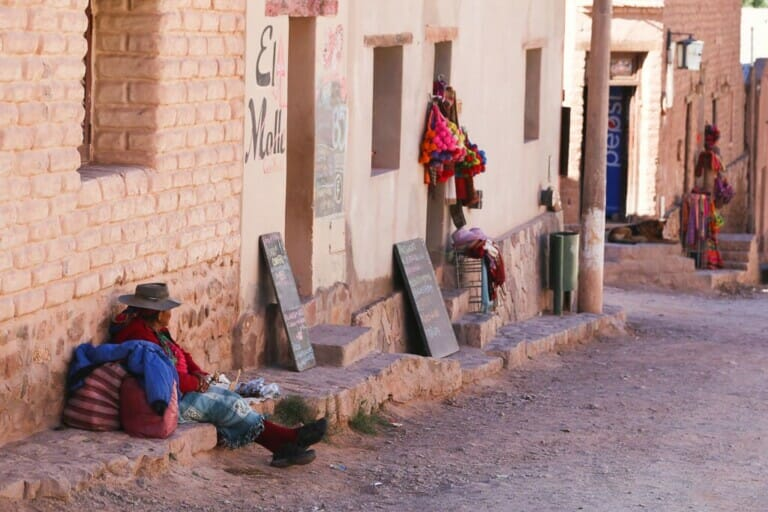 A woman sits on the side of a dirt road next to stucco buildings