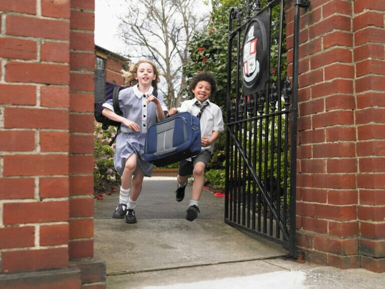 Two school children in private school uniforms run out of a gate to leave school