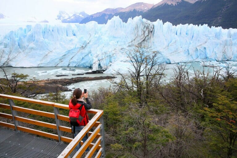 A woman takes a picture of a glacier with her phone