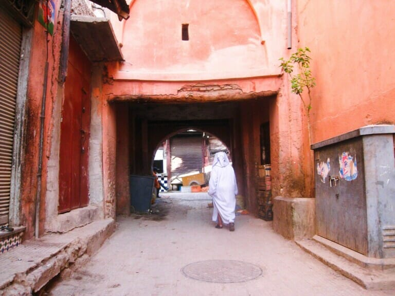 A woman walks under an archway