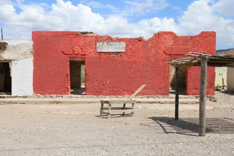 The remains of a ruined red adobe building in the desert