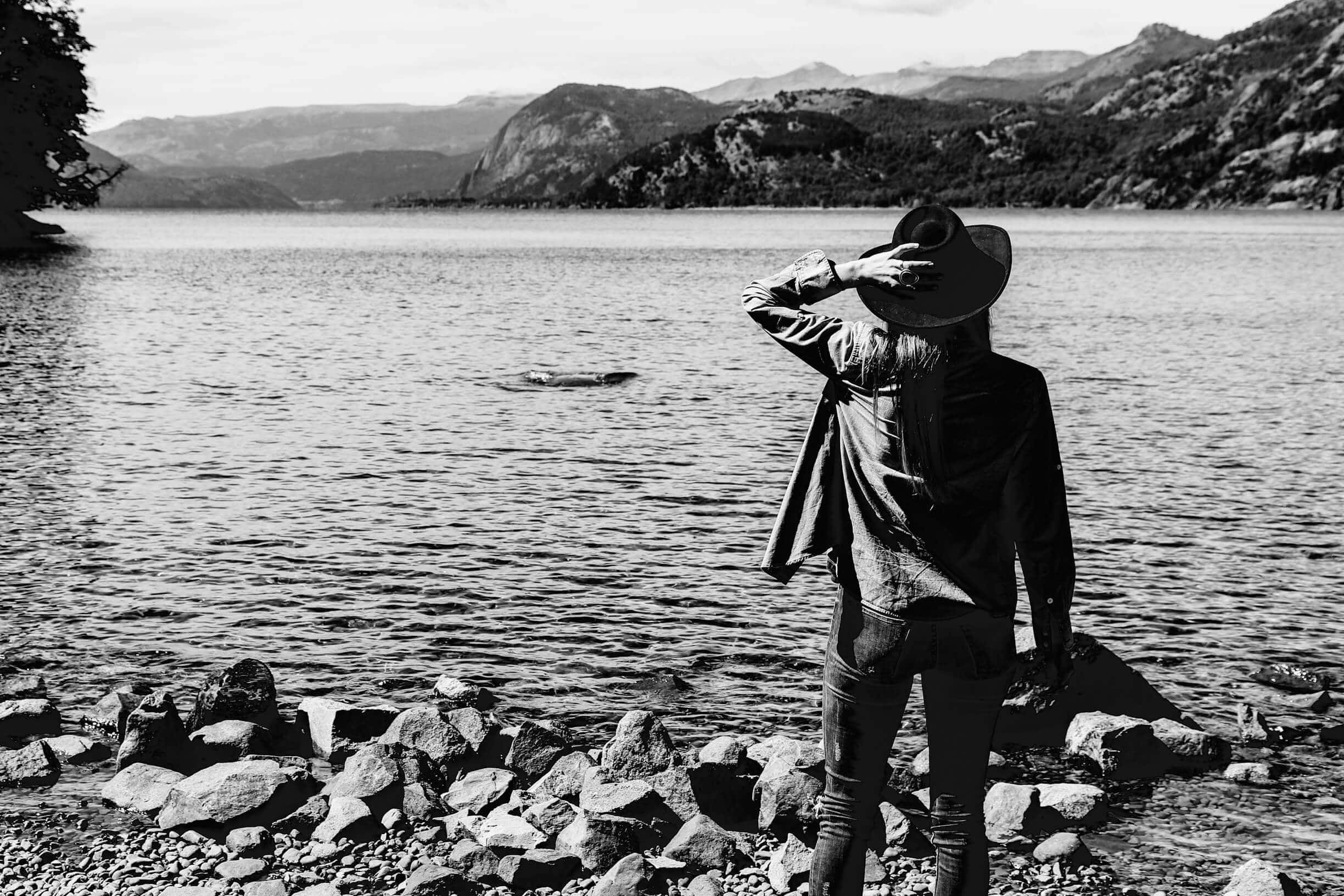 A black and white image of a woman with her back to the camera in front of a lake