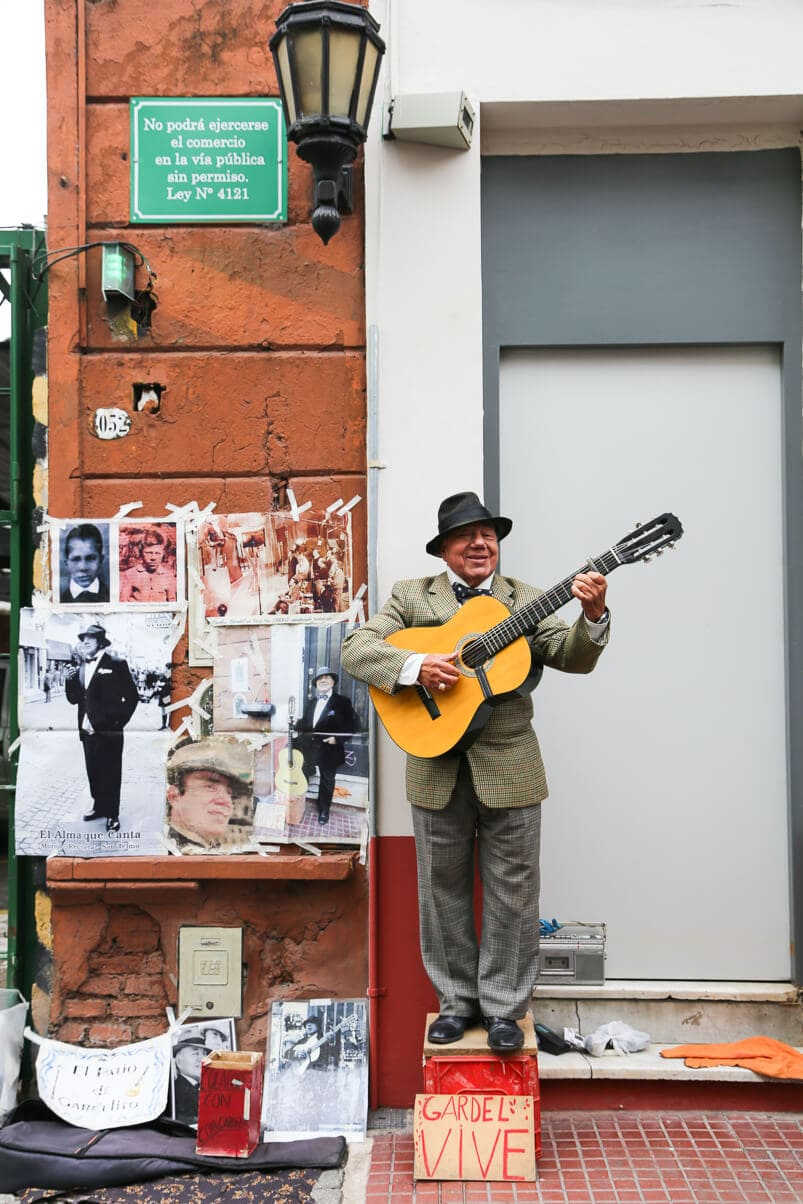 A man stands on a box playing the guitar