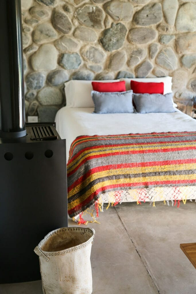 A bed with a quilt in front of a wall of river stones