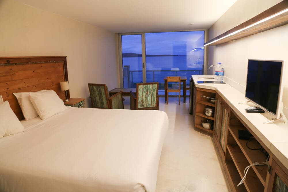 A king size bed in a hotel room by the ocean