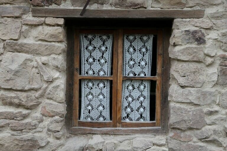 A lace curtain in a wooden window frame in a stone wall