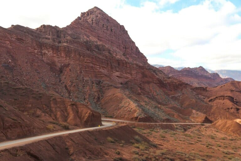 A highway in the desert clings to a red mountain