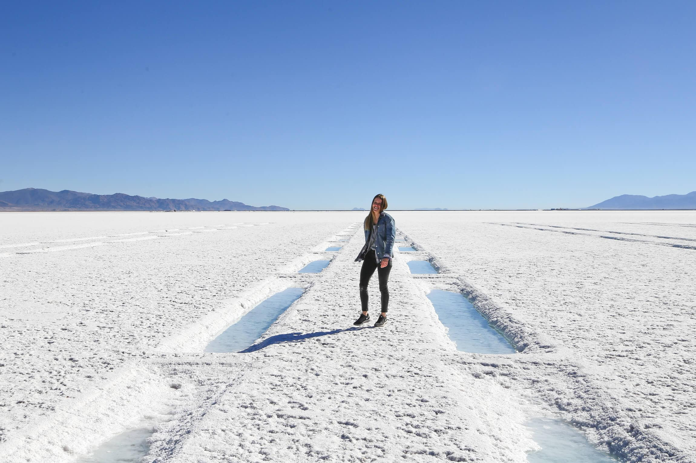 A woman walks between puddles of water on salt falts in Argentina