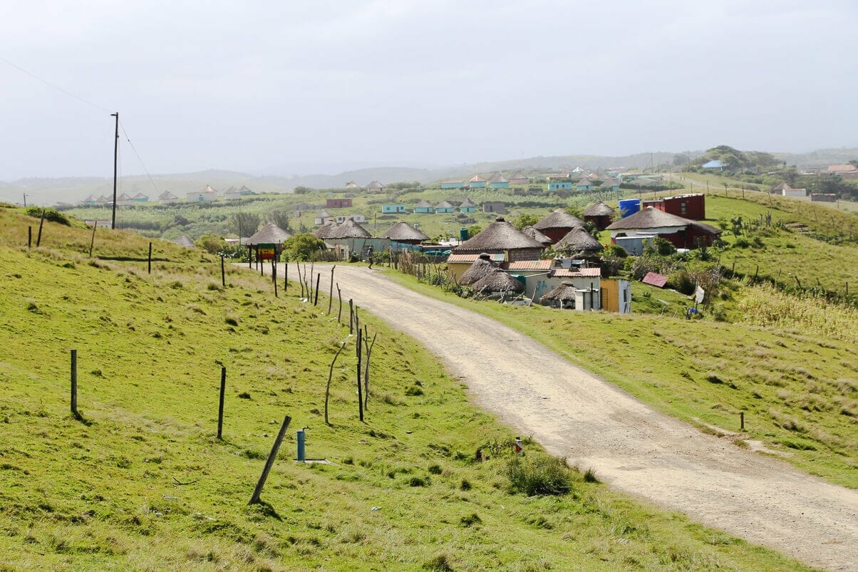 A road leads to a collection of small huts