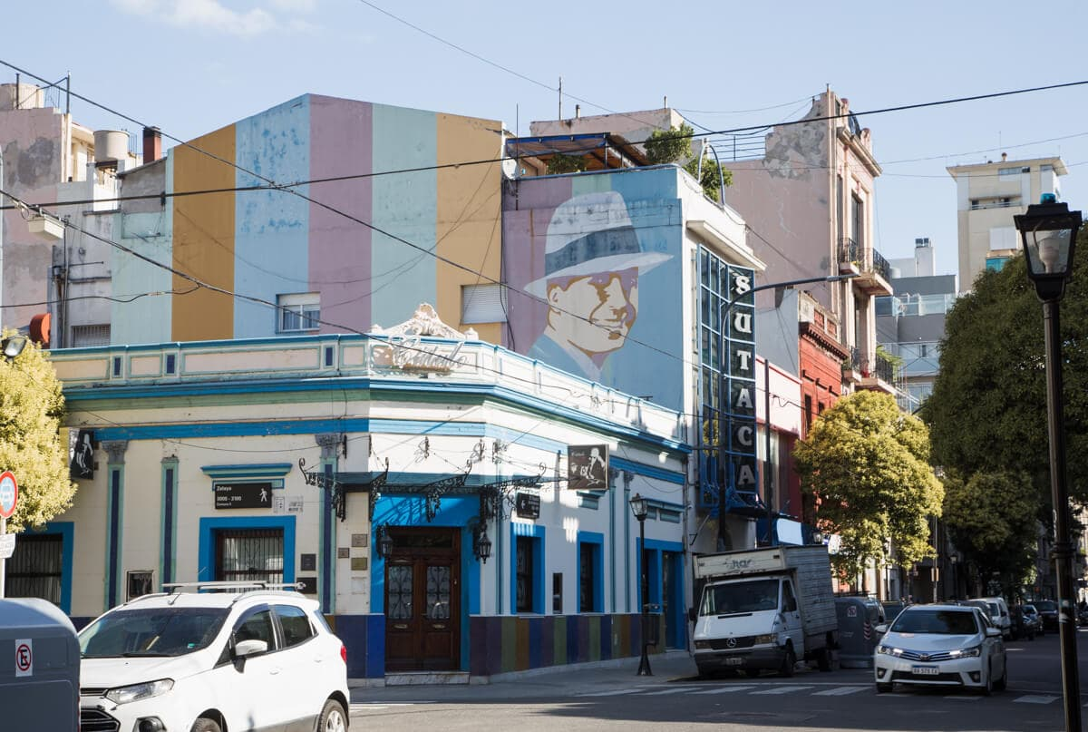 Cars drive by a street corner with a carlos gardel mural painted on the upper floors