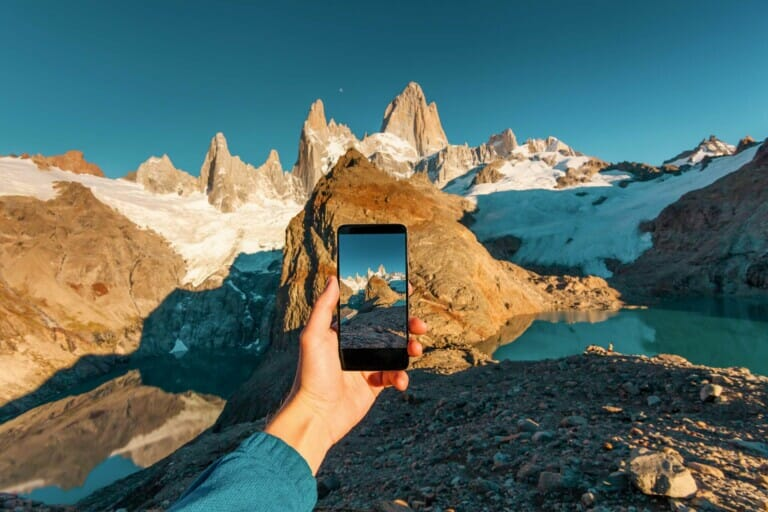 A hand holds a phone out in front of them in front of the mountains in Patagonia
