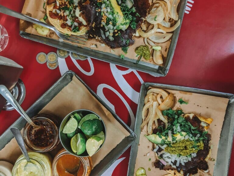 Three platters of tacos on a red table