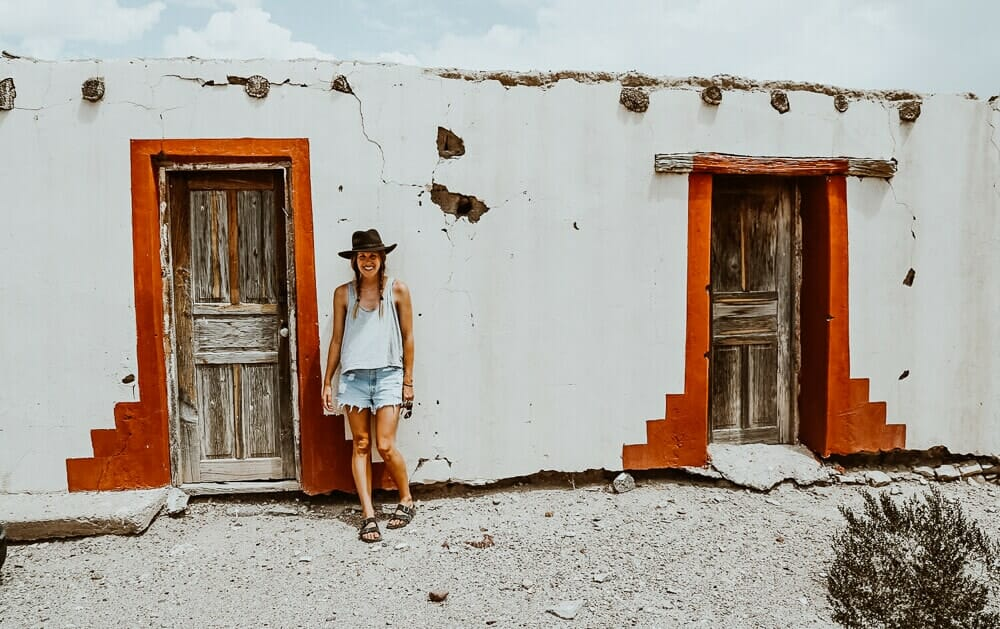 A woman leans against a red and white stucco building in the desert
