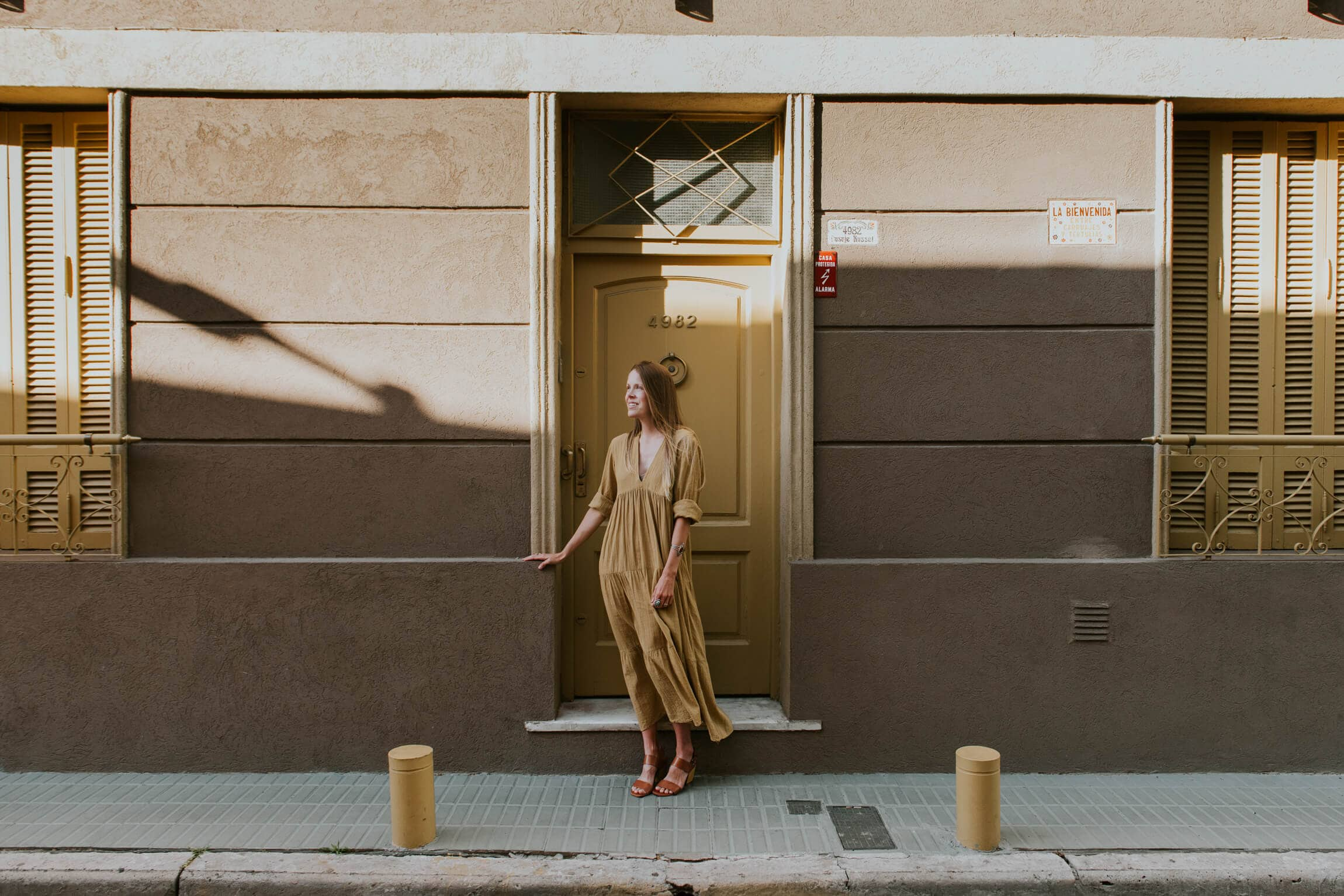 A woman in a yellow dress stands in front of a monochrome beige home