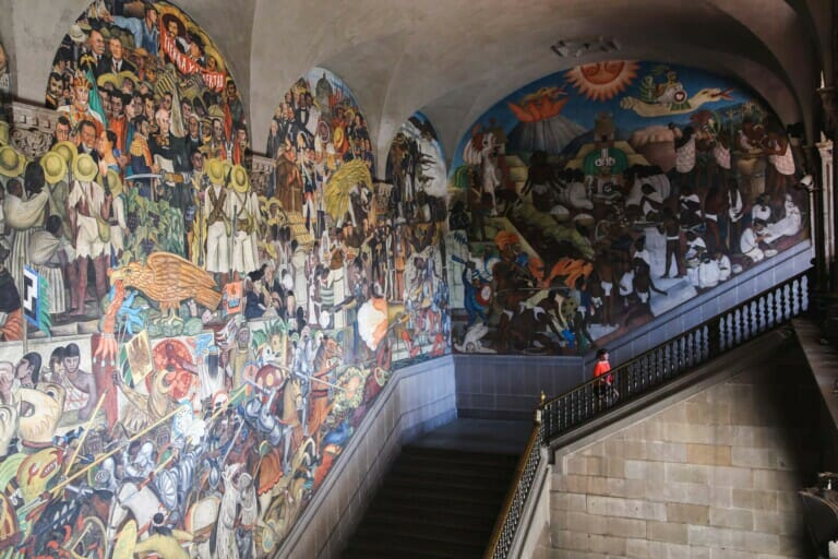 A woman in an orange shirt walks up the stairs in front of Diego Rivera murals in Mexico City