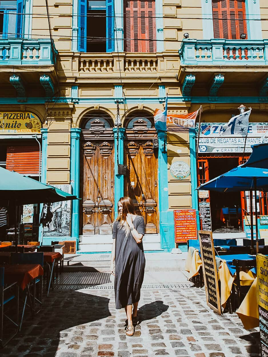 A woman walks down a cobblestone street in front of a yellow building