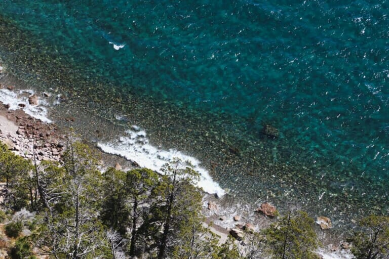 An aerial photo of a crystal clear lake washing up to a rocky beach