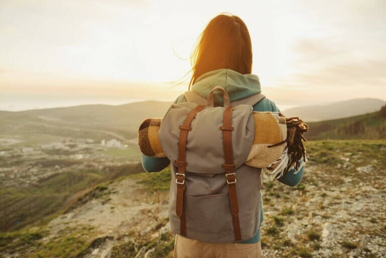 A woman with a backpack on in the countryside has her back to the camera