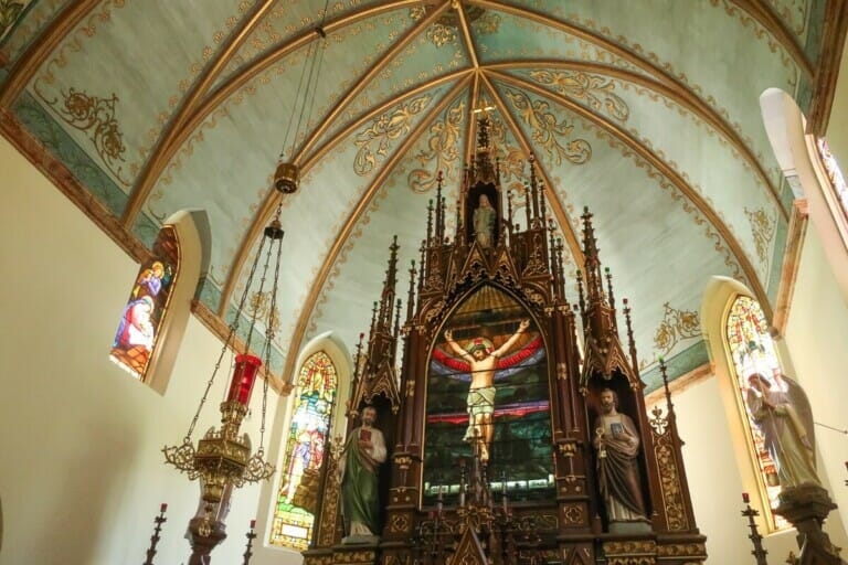 A statue of Jesus hangs from a wooden alter in a church