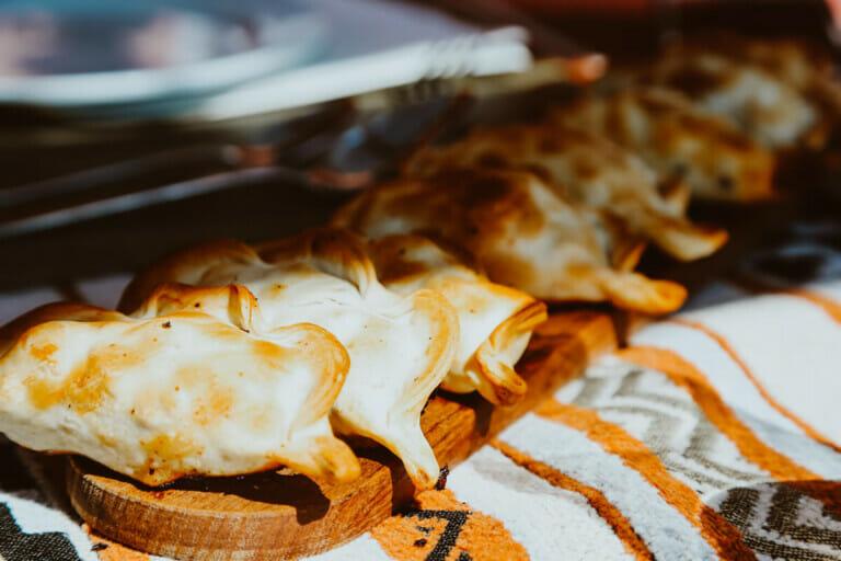 A tray of empanadas on a woven table cloth